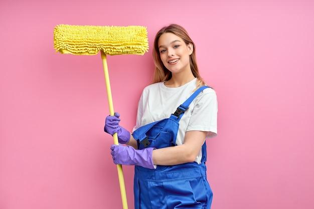 Piacevole casalinga di buon umore con in mano attrezzature per la pulizia, straccio per il pavimento, con indosso un'uniforme blu
