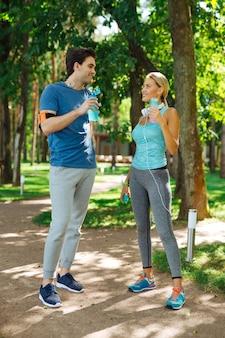 Piacevole interazione. persone positive e allegre che conversano piacevolmente durante il riposo durante un allenamento