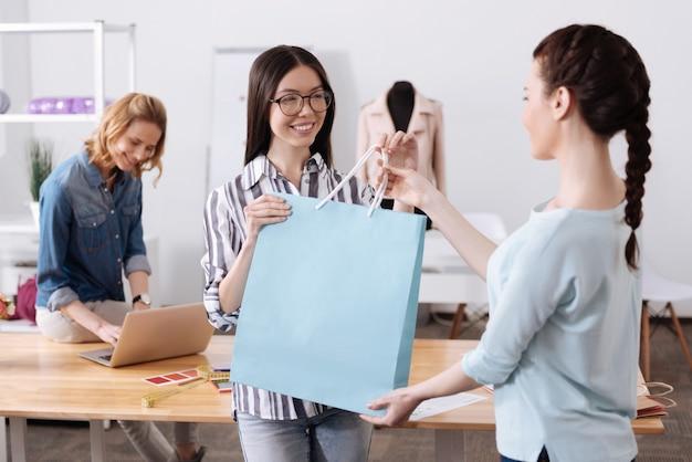 Piacevole donna allegra che accetta una grande borsa blu con un vestito da un operaio di atelier mentre il suo collega lavora su un computer portatile