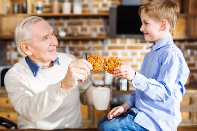 Piacevole ragazzino che mangia pasticceria fatta in casa con il nonno mentre riposa a casa