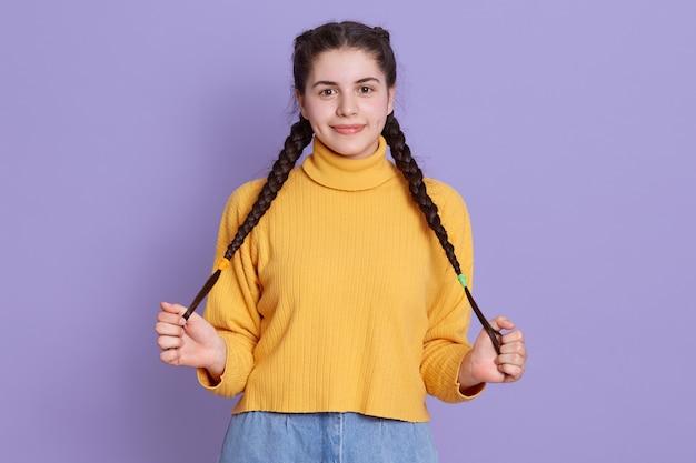 La ragazza caucasica allegra sembrante piacevole tiene entrambe le mani sulle sue trecce