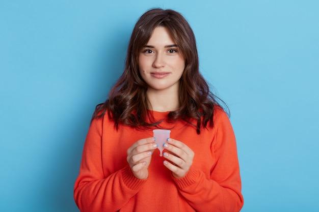 Piacevole ragazza dai capelli scuri con espressione calma che tiene la coppetta mestruale, guardando direttamente la fotocamera, isolata sopra la parete blu.