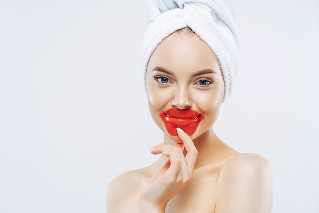 Una donna dall'aspetto piacevole e in salute tiene le macchie sulle labbra, indossa un asciugamano sulla testa, ha una pelle pulita e pura dopo la procedura igienica, sta a torso nudo contro il muro bianco, spazio vuoto per la tua pubblicità