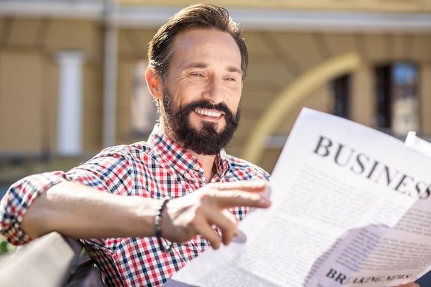 Piacevole mattinata. allegro uomo adulto sorridente durante la lettura di un quotidiano