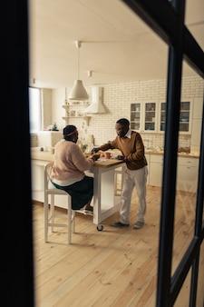 Piacevole mattinata. bella coppia di sposi seduti attorno al tavolo mentre si fa colazione al mattino
