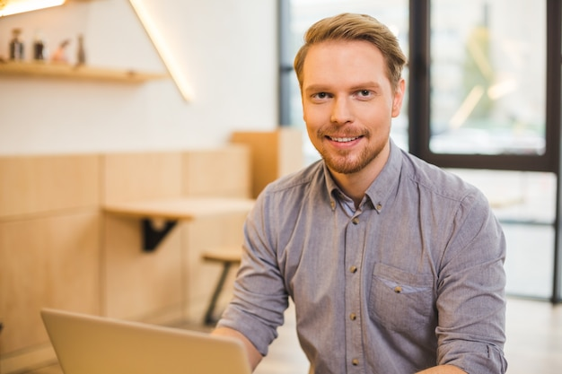 Piacevole simpatico uomo barbuto che sorride e ti guarda mentre lavora al laptop