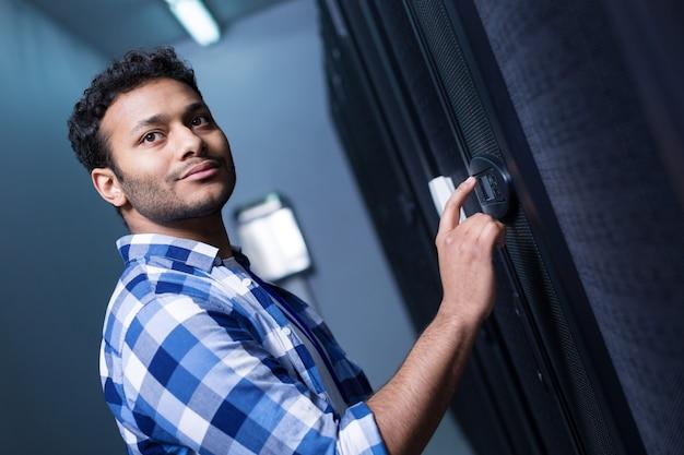 Piacevole simpatico uomo positivo in piedi ordinato sul pannello degli indicatori e premendo il pulsante su di esso durante l'impostazione della serratura elettronica