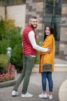 Piacevole coppia positiva che si rivolge a te mentre stai insieme per strada