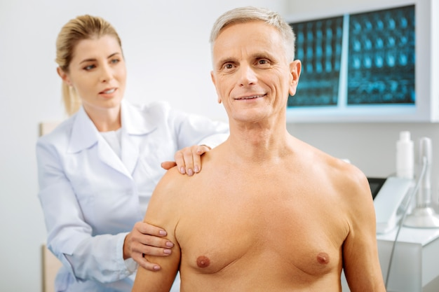 Piacevole procedura. uomo invecchiato allegro felice che sorride e che è di buon umore mentre visita un ospedale