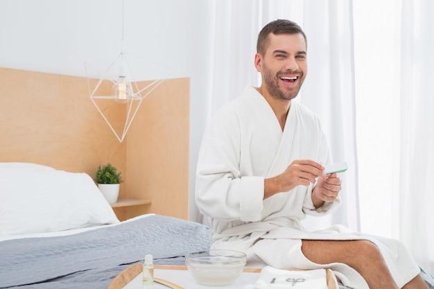 Piacevole relax. felice gioioso uomo seduto sul letto mentre si tiene una lima per unghie
