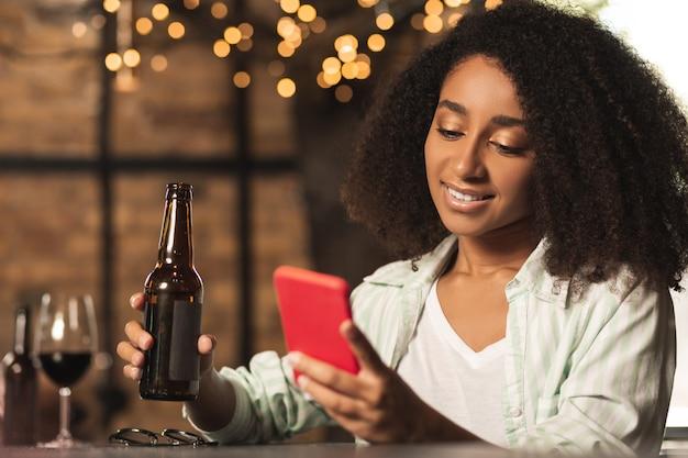 Piacevole e rilassante. attraente donna riccia seduta al bancone del bar e utilizzando il suo telefono mentre beve birra