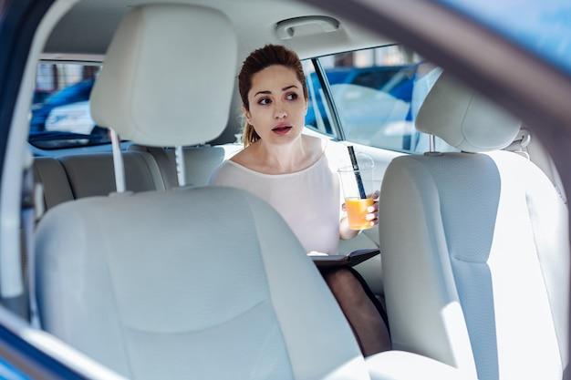 Piacevole corsa. attraente bella piacevole donna seduta sul sedile posteriore della macchina e bere succo d'arancia mentre si tiene un notebook