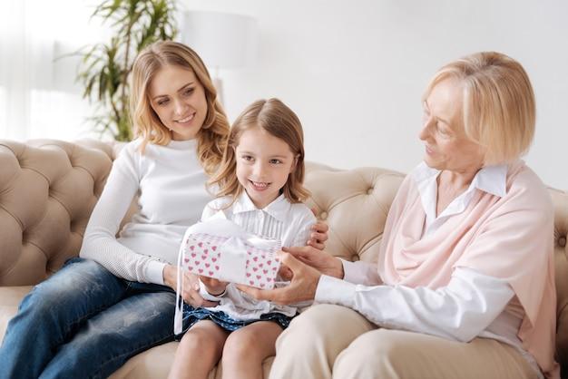 Piacevole donna senior distribuendo una confezione regalo legata con un nastro bianco alla sua graziosa nipotina seduta nell'abbraccio della madre