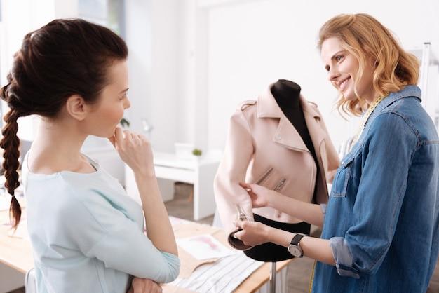 Piacevole donna sorridente che tocca la manica di una giacca oltre a mostrarla alla collega appoggiando il mento sulle dita con espressione pensierosa