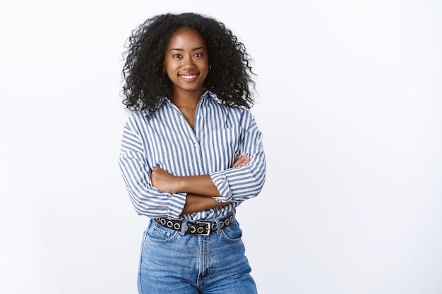 Piacevole successo di bell'aspetto donna afroamericana responsabile dell'ufficio gestione del lavoro rilassante all'ora di pranzo sorridente ampiamente parlando amichevole braccia incrociate petto sicuro di sé soddisfatto, muro bianco
