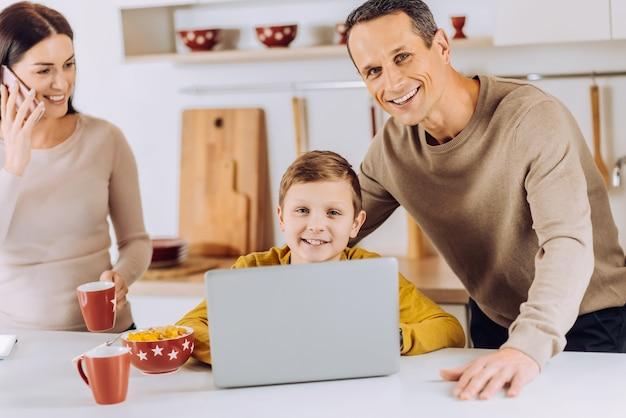 Piacevole supervisione. allegro padre amorevole in posa con suo figlio e controllando il suo lavoro di progetto sul laptop mentre sua moglie parla al telefono