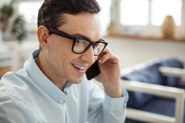 Discorsi piacevoli. uomo dai capelli scuri dagli occhi scuri di bell'aspetto che sorride e parla al telefono e indossa gli occhiali