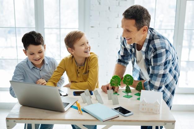 Piacevole visita. gioiosi ragazzi pre-adolescenti in piedi a guardare la presentazione del progetto del padre sul laptop e discuterne allegramente con lui mentre visitava il padre nel suo ufficio