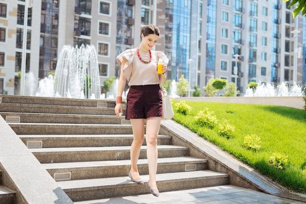 Piacevole passeggiata. attraente giovane donna scendendo le scale tenendo una bottiglia di succo di frutta