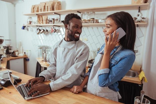 Piacevole giornata di lavoro. due piacevoli baristi in grembiule in piedi dietro il bancone del caffè, l'uomo che aggiorna il menu sul sito web mentre la donna parla al telefono