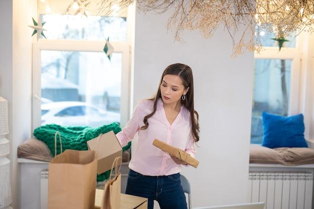 Piacevole giovane donna che tiene una confezione regalo mentre compra i regali per i suoi amici