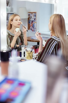 Piacevole giovane donna che si guarda allo specchio mentre si trucca