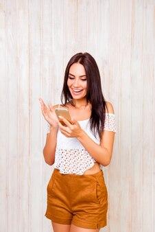 Ragazza graziosa piacevolmente sorpresa che legge il messaggio sullo smartphone