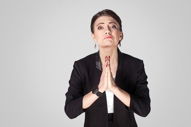 Mi aiuti per favore. donna scusa e scusa. foto in studio, al coperto. isolato su sfondo grigio