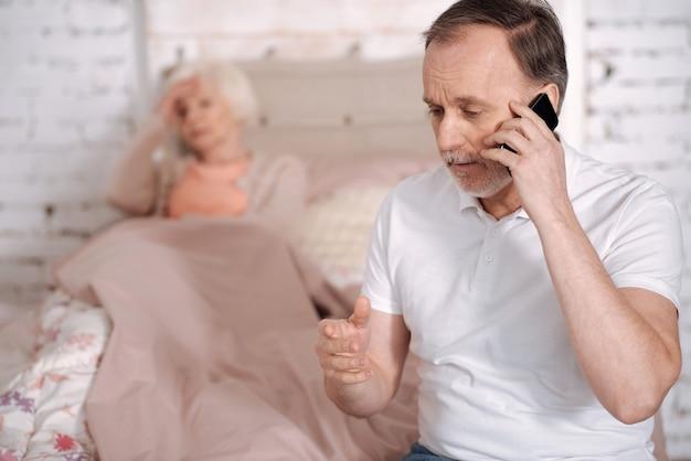 Per favore, faccia in fretta. ritratto di uomo anziano che chiama emergenza mentre sua moglie malata sdraiata su ben con un terribile mal di testa.