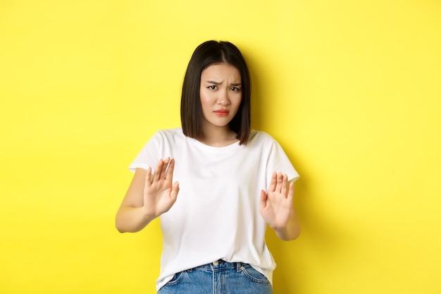 Per favore no. donna asiatica, vittima di aggressioni o abusi domestici, implorando con le mani alzate in difesa, accigliata triste, implorando stop, in piedi su sfondo giallo