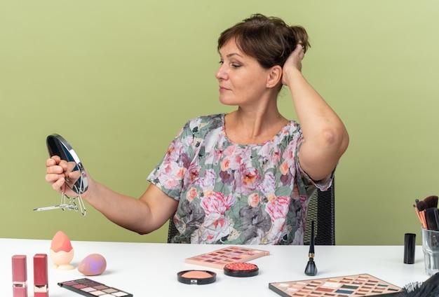 Donna caucasica adulta contenta seduta al tavolo con strumenti per il trucco che si mette la mano sulla testa tenendo e guardando lo specchio