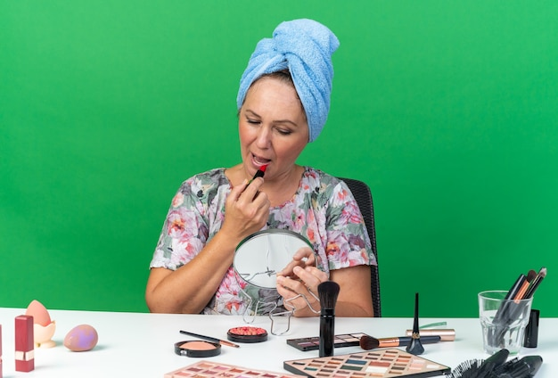 Donna caucasica adulta contenta con i capelli avvolti in un asciugamano seduto al tavolo con strumenti per il trucco che applicano rossetto tenendo e guardando lo specchio