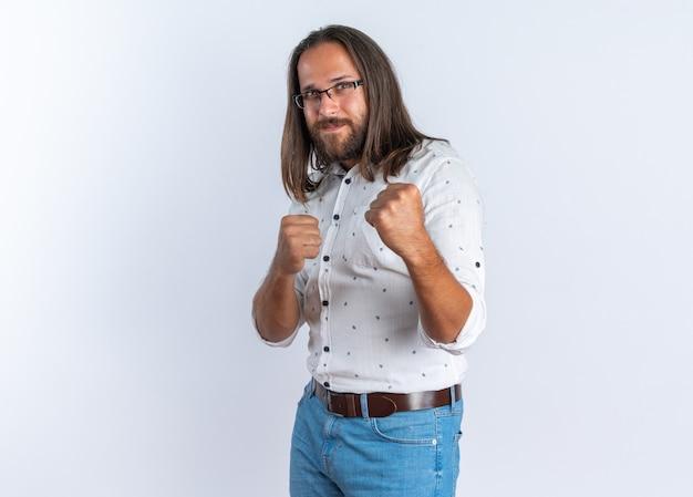 Piacere adulto bell'uomo con gli occhiali in piedi in vista di profilo guardando la telecamera facendo gesto di boxe isolato sul muro bianco con copia spazio