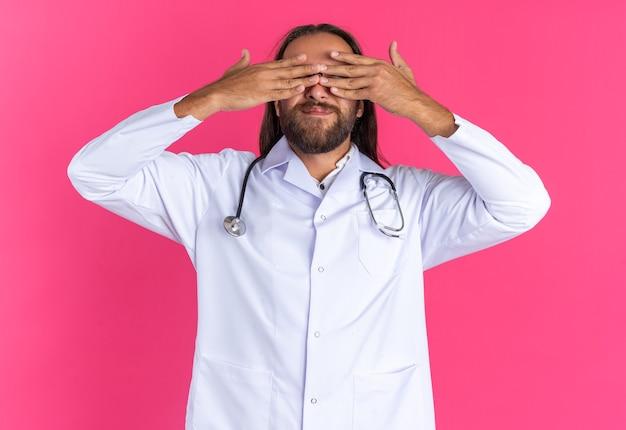 Felice maschio adulto medico che indossa abito medico e stetoscopio con occhiali che coprono gli occhi con le mani isolate sulla parete rosa