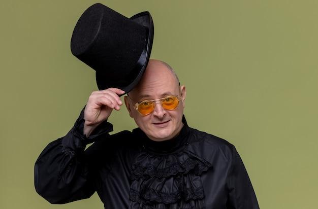 Uomo slavo adulto soddisfatto con occhiali da sole in camicia gotica nera con cappello a cilindro nero