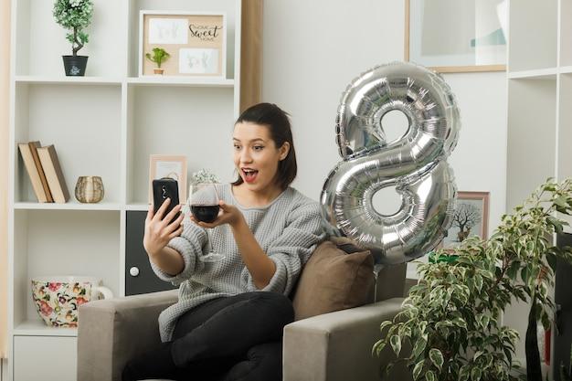 Piacevole bella ragazza in una felice giornata delle donne con in mano un bicchiere di vino, scatta un selfie seduto sulla poltrona in soggiorno