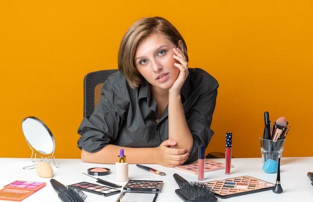 Una bella donna contenta si siede al tavolo con gli strumenti per il trucco mettendo la mano sulla guancia