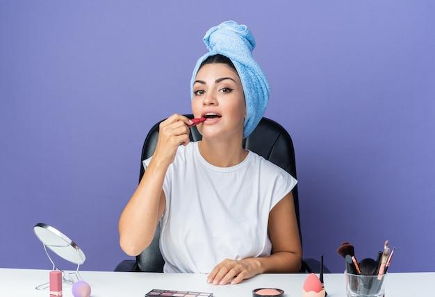 Una bella donna contenta si siede al tavolo con gli strumenti per il trucco avvolti i capelli in un asciugamano applicando il rossetto