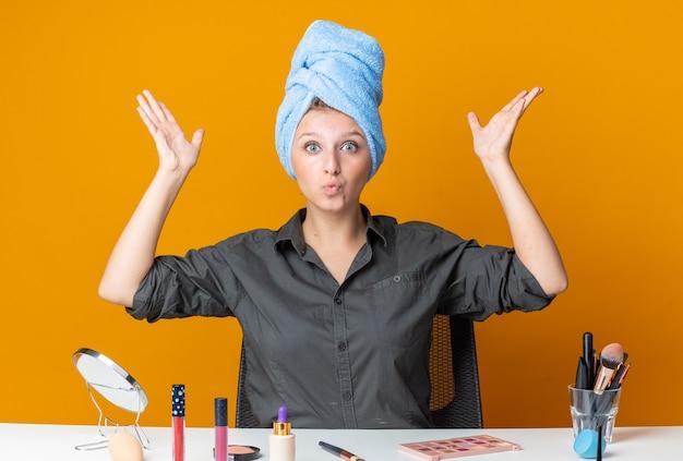 Una bella donna contenta si siede al tavolo con gli strumenti per il trucco avvolti i capelli in un asciugamano allargando le mani