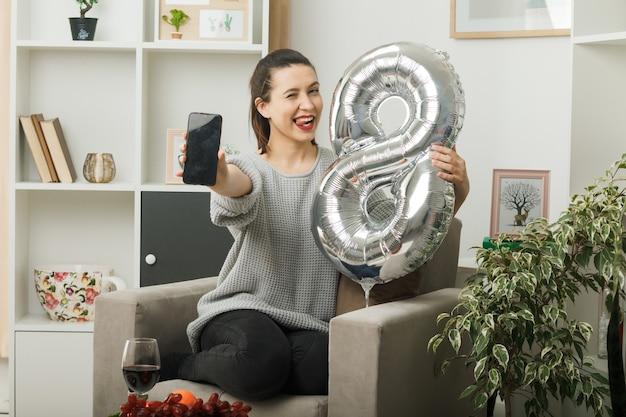 Felice sbatté le palpebre bella ragazza nel giorno delle donne felici con in mano il palloncino numero otto con il telefono seduto sulla poltrona in soggiorno