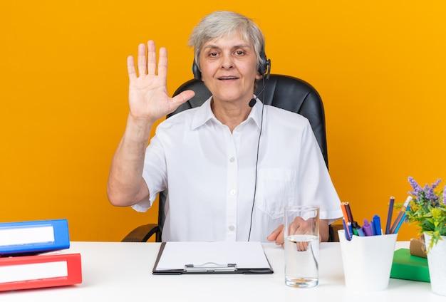 Piacevole operatore di call center femminile caucasico sulle cuffie seduto alla scrivania con strumenti da ufficio che alzano la mano