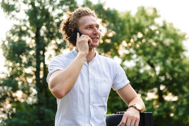 Soddisfatto uomo d'affari ricci con valigetta parlare tramite smartphone e distogliere lo sguardo mentre è seduto su una panchina nel parco