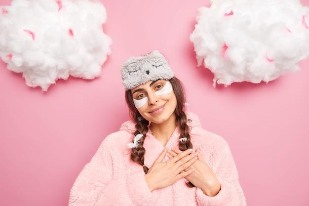 La donna bruna lieta e lieta inclina la testa fa il gesto di gratitudine indossa la maschera del sonno e il caldo pigiama gode del nuovo giorno isolato sopra il muro rosa con le nuvole sopra