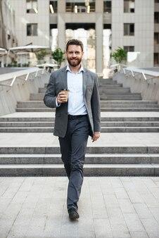 Felice imprenditore uomo in abito grigio scendendo le scale del moderno centro business, con caffè da asporto in mano
