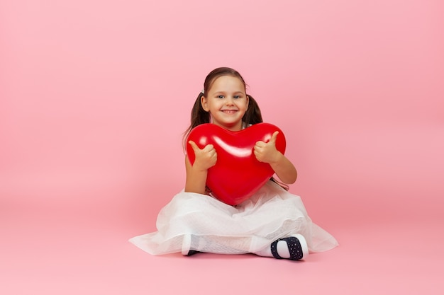Contento bambino felice in abito bianco tiene un palloncino rosso a forma di cuore e dà un pollice in alto