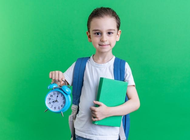 Felice ragazzino che indossa uno zaino con in mano un libro e una sveglia guardando la telecamera isolata sul muro verde