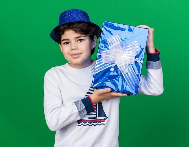 Felice ragazzino che indossa un cappello da festa blu che tiene una scatola regalo intorno al viso