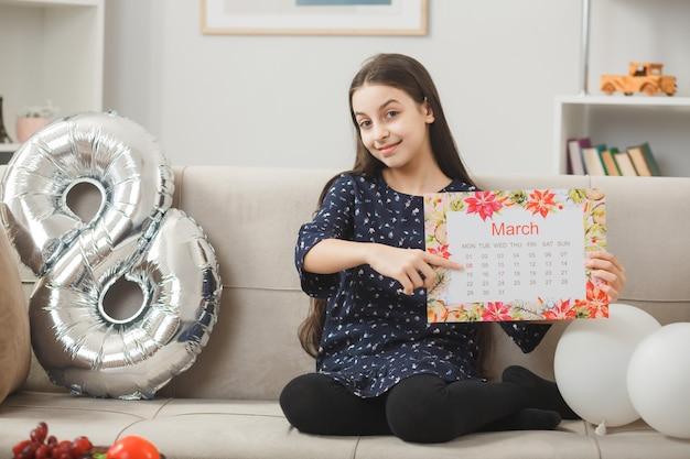 Bambina contenta per la felice festa della donna che tiene e indica carlendar seduto sul divano nel soggiorno