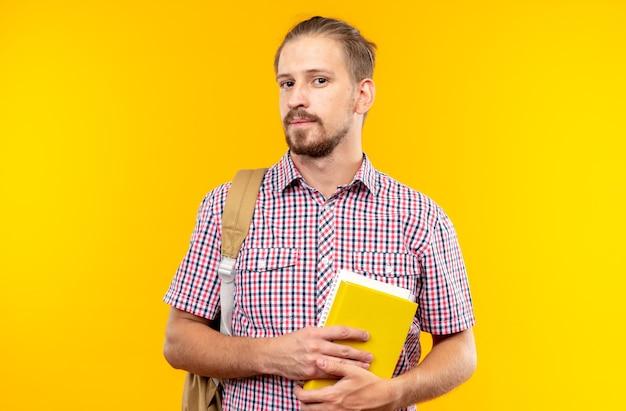 Soddisfatto della fotocamera giovane studente che indossa uno zaino con in mano un libro isolato su una parete arancione