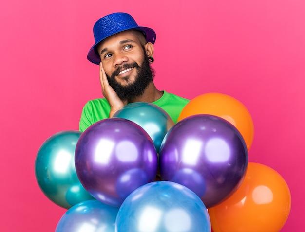 Felice guardando lato giovane ragazzo afro-americano che indossa un cappello da festa in piedi dietro palloncini isolati sul muro rosa